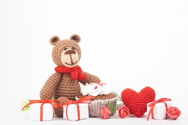 Orso a maglia con un cuore. decorazioni di san valentino. giocattolo a maglia, amigurumi, biglietto di auguri. Foto Premium