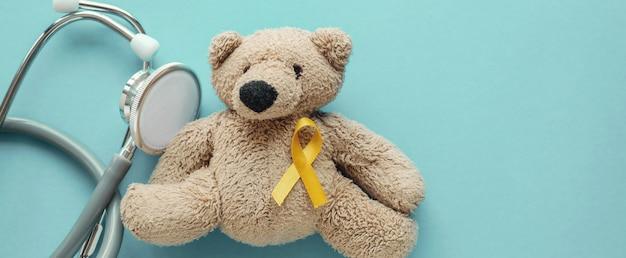 Orso bruno di peluche per bambini con nastro e stetoscopio in oro giallo Foto Premium