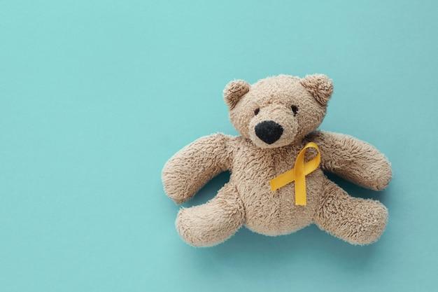 Orso bruno di peluche per bambini con nastro in oro giallo Foto Premium