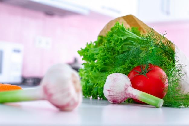 Ortaggi freschi organici in sacco di carta per cucinare piatti a base di verdure e insalate in cucina Foto Premium