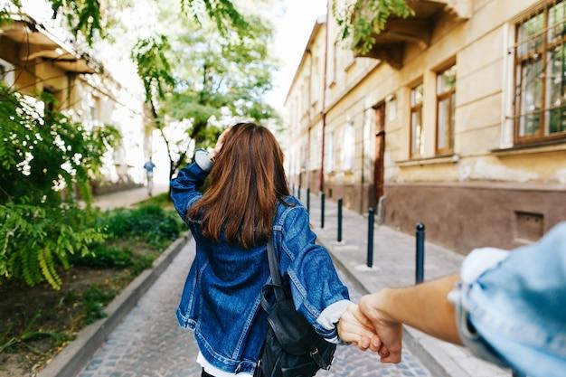 Osservi da dietro alla giovane donna che tiene la mano dell'uomo nella posa 'seguimi' Foto Gratuite
