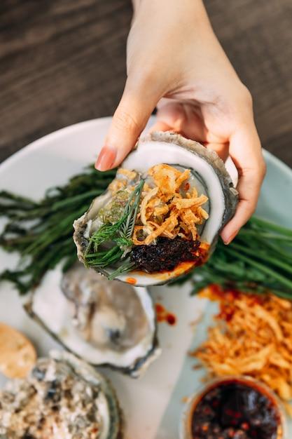Ostrica fresca con guscio in mano che condimento con scalogno fritto, pasta di peperoncino, acacia pennata e salsa di frutti di mare in stile tailandese. Foto Premium