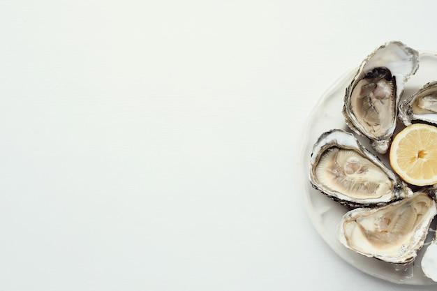 Ostrica fresca con limone su un piatto Foto Gratuite