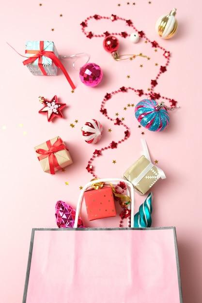 Pacchetto con diverse decorazioni natalizie su rosa Foto Premium