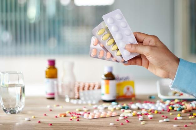 Pacchetto della pillola delle medicine della tenuta della mano con la diffusione variopinta delle droghe Foto Premium