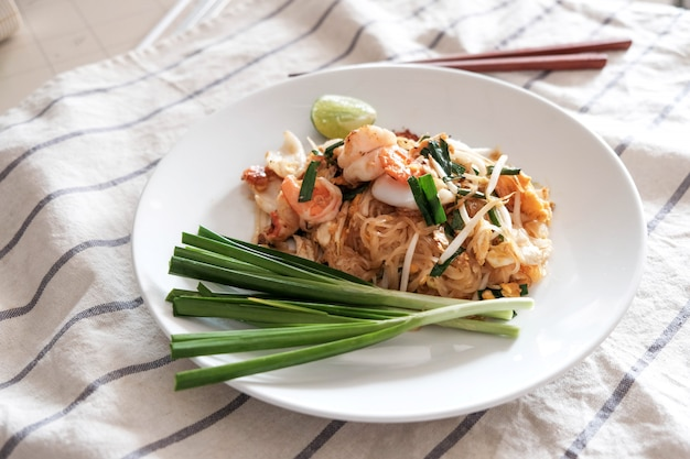 Pad thai, gamberi, calamari, con peperoncino, lime e verdure sul lato Foto Premium