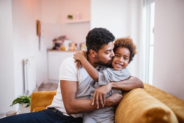 Padre afroamericano felice e piccola figlia sveglia a casa. abbracciare e baciare. Foto Premium