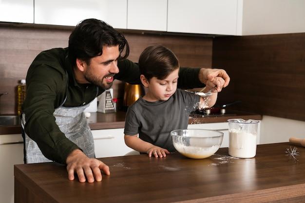 Padre aiutando il figlio a fare la pasta Foto Gratuite
