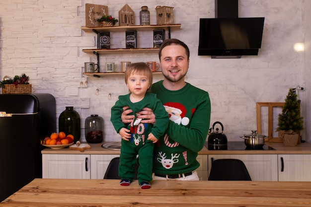 Padre che abbraccia il suo bambino nella cucina di natale a casa. Foto Premium