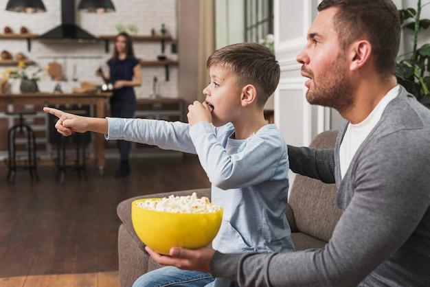 Padre che guarda un film con il figlio Foto Gratuite