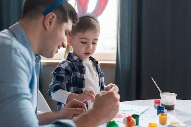 Padre che mostra a suo figlio come dipingere le uova di pasqua Foto Gratuite