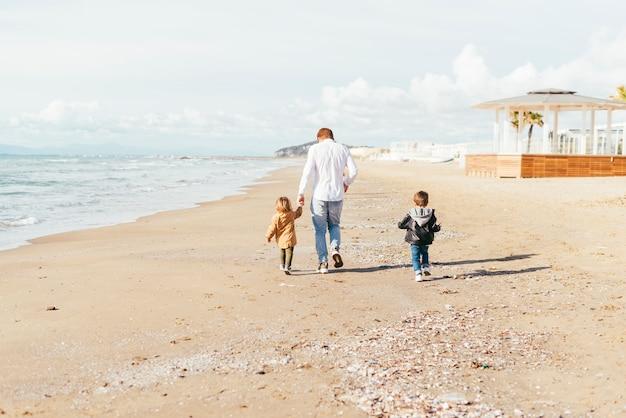 Padre con figli che passeggiano lungo la spiaggia Foto Gratuite