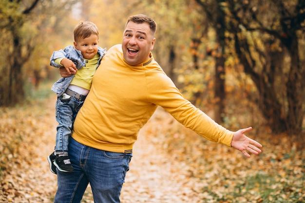 Padre con figlio nel parco d'autunno Foto Gratuite