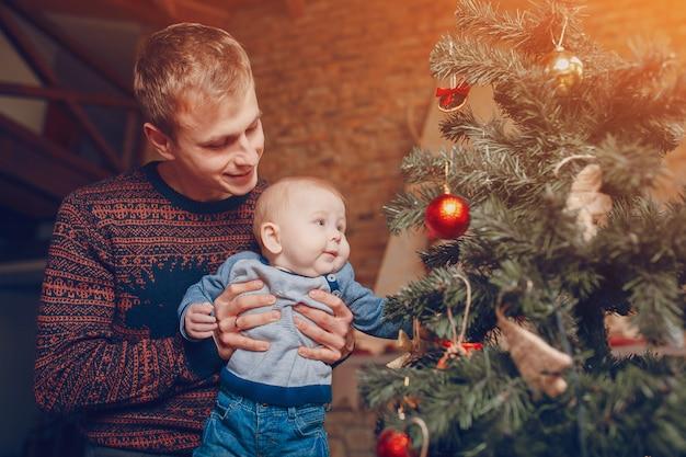 Padre con il suo bambino in braccio guardando le alberi di natale Foto Gratuite