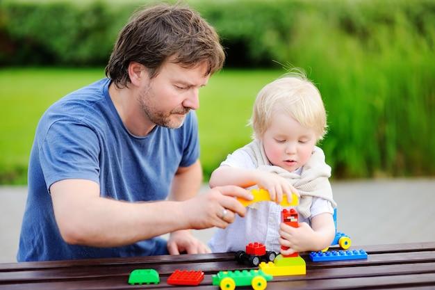 Padre di mezza età con suo figlio bambino giocando con blocchi di plastica colorata Foto Premium