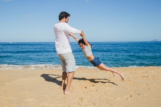 Padre e figlia che giocano sulla spiaggia Foto Gratuite