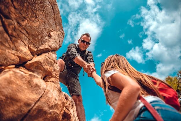 Padre e figlia che si arrampicano sulla scogliera Foto Premium