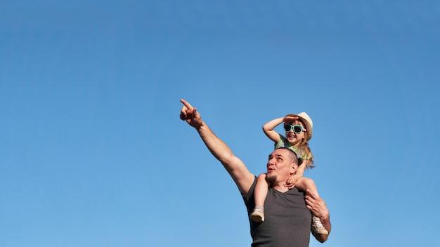 Padre e figlia sulle spalle gioiscono felicemente. Foto Premium