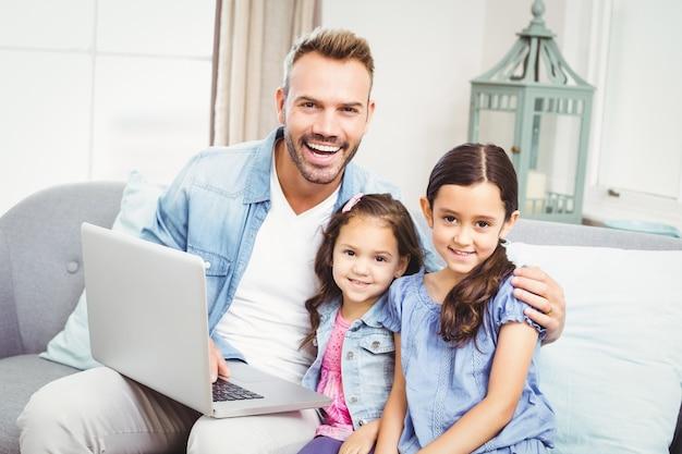 Padre e figlie con il portatile seduti sul divano Foto Premium