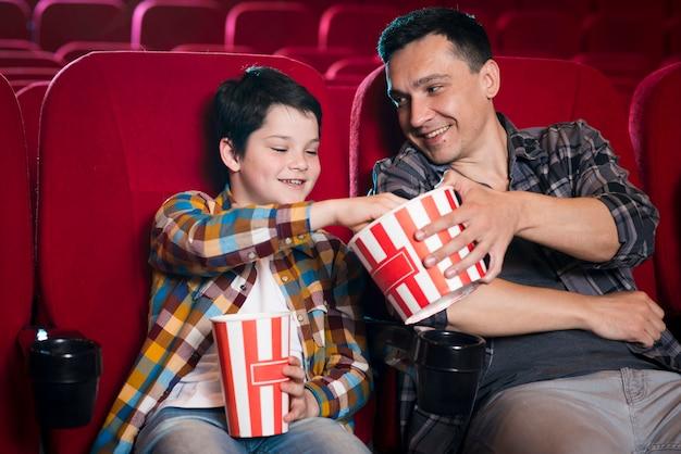 Padre e figlio a guardare film nel cinema Foto Gratuite