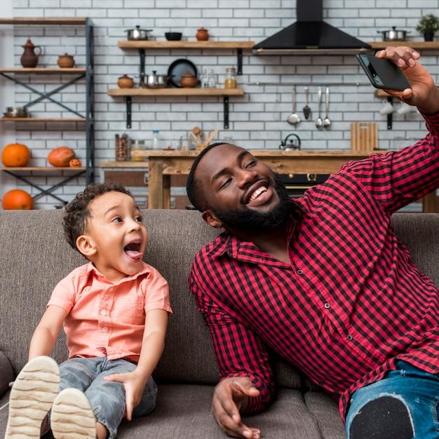 Padre e figlio allegri neri che prendono selfie Foto Gratuite