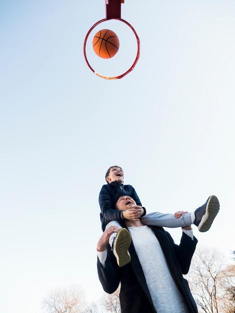 Padre e figlio che giocano a pallacanestro vista bassa Foto Gratuite