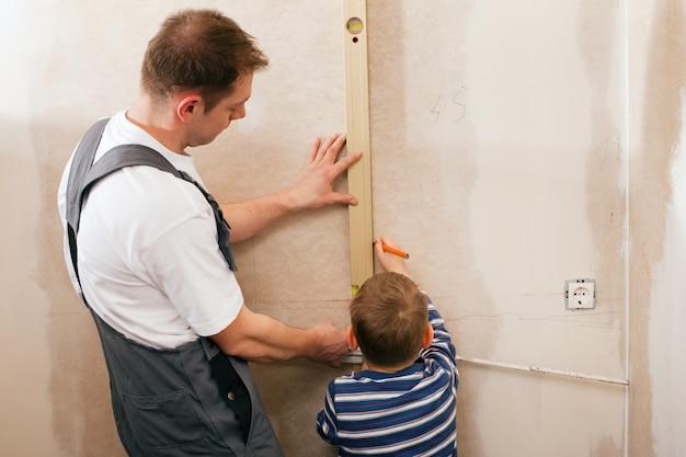 Padre e figlio che misurano muro a secco Foto Premium
