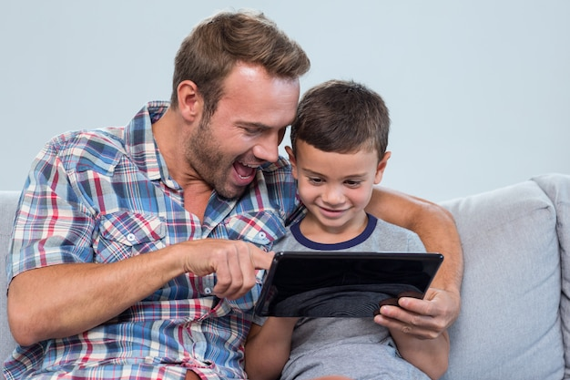 Padre e figlio che per mezzo della compressa digitale Foto Premium