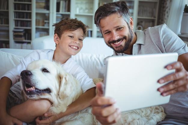 Padre e figlio che si siedono sul sofà con il cane e che per mezzo della compressa digitale Foto Premium