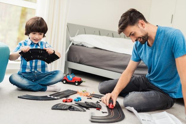 Padre e figlio competono in gare con macchine per bambini. Foto Premium