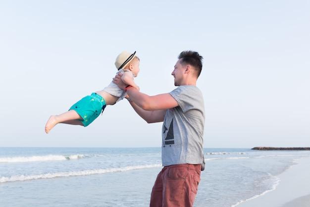 Padre e figlio divertirsi su una spiaggia Foto Premium