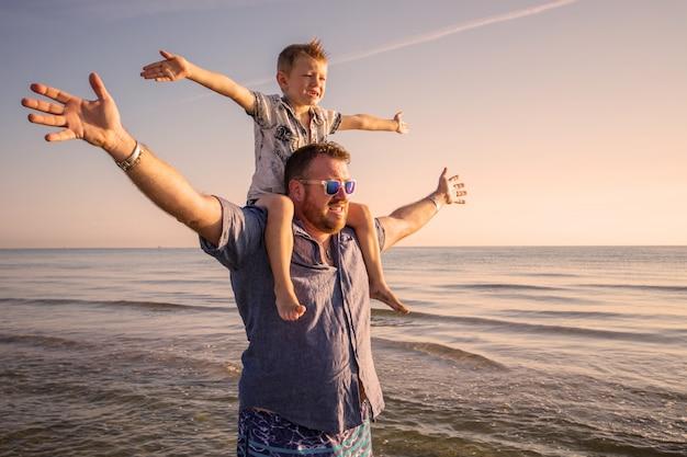 Padre e figlio felici che hanno tempo della famiglia sulla spiaggia sul tramonto Foto Premium