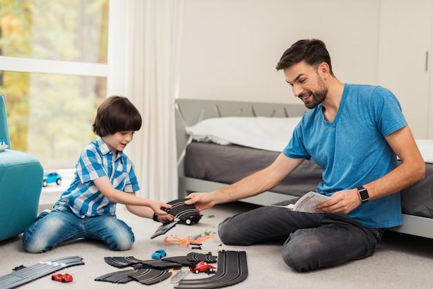 Padre e figlio gareggiano in gare con auto per bambini Foto Premium