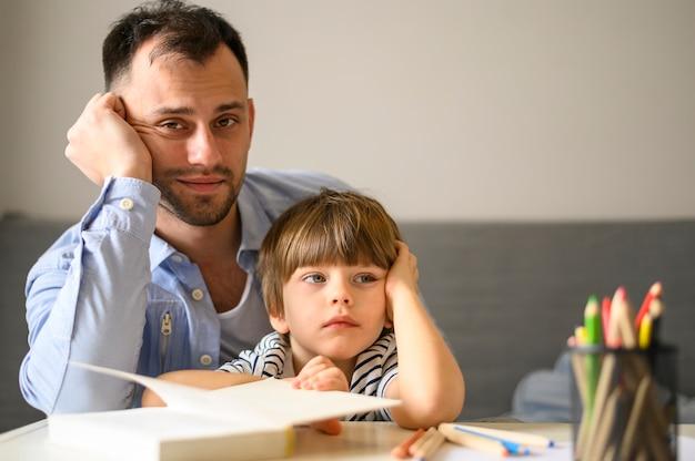 Padre e figlio in posa con il libro Foto Gratuite