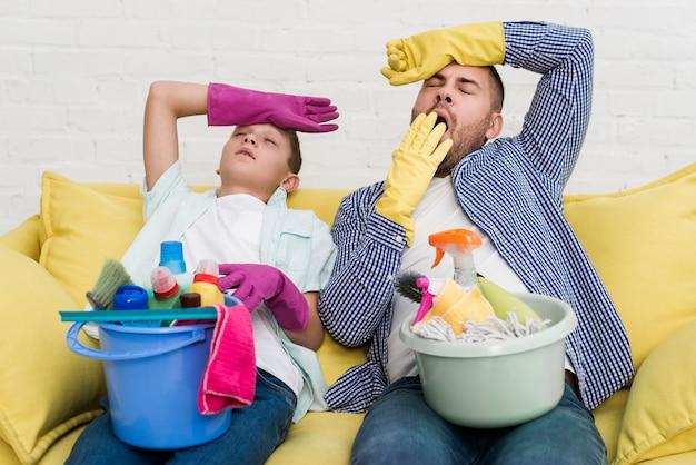 Padre e figlio sonnolenti che riposano sul sofà dopo la pulizia della casa Foto Gratuite