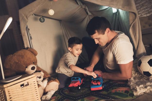 Padre e figlio stanno giocando con le auto di notte. Foto Premium