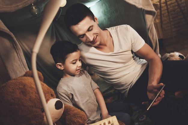 Padre e figlio stanno guardando film sul tablet di notte a casa Foto Premium