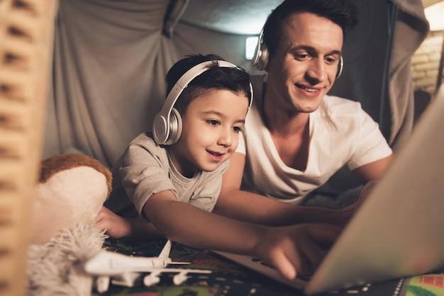 Padre e figlio stanno parlando su skype alla famiglia sul computer portatile. Foto Premium