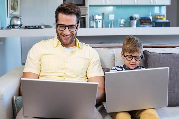 Padre e figlio utilizzando computer portatili sul divano a casa in salotto Foto Premium