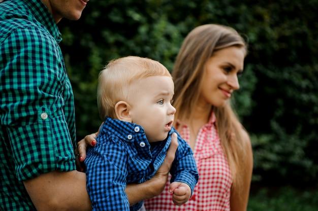 Padre e madre felici che tengono sulle mani un neonato con Foto Premium
