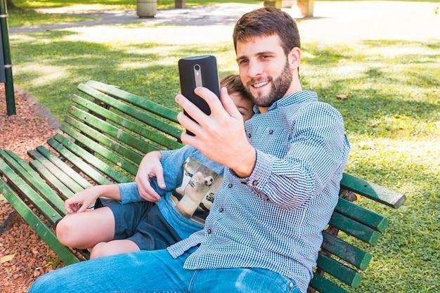 Padre felice che prende selfie con suo figlio sul telefono cellulare nel parco Foto Gratuite