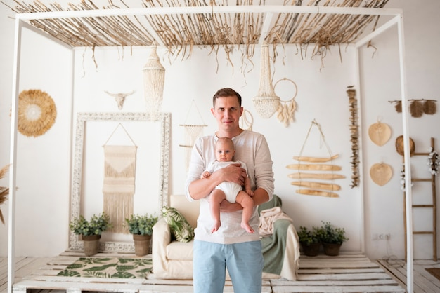 Padre felice che tiene neonato Foto Gratuite