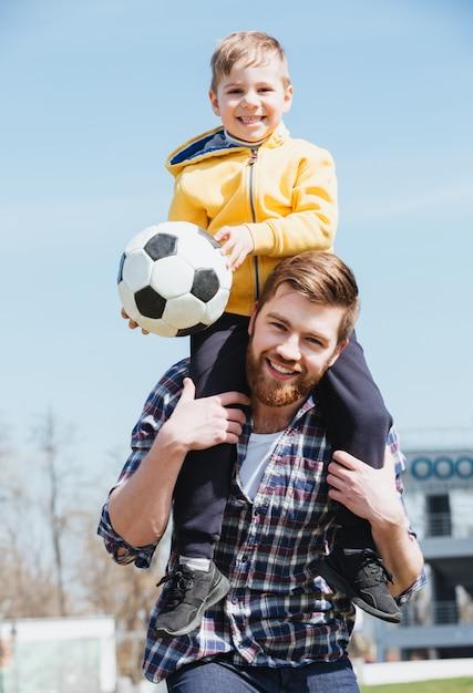Padre felice che trasporta il suo piccolo figlio sulle spalle Foto Gratuite