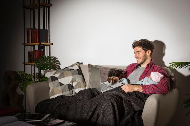 Padre felice con il bambino usando il portatile in serata Foto Gratuite