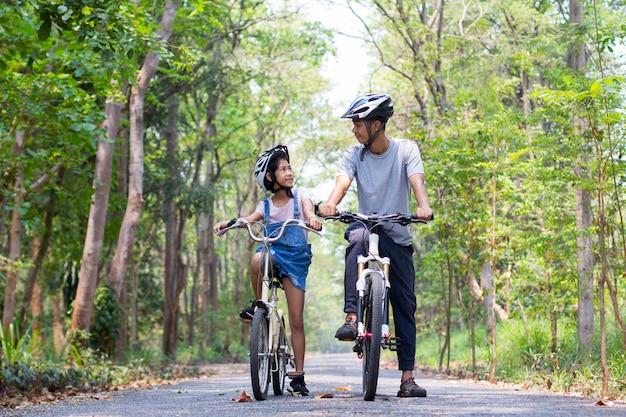 Padre felice e figlia che ciclano nel parco Foto Premium
