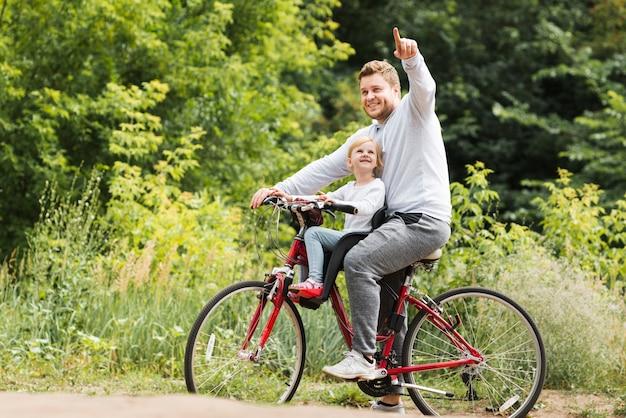 Padre in bicicletta che punta per la figlia Foto Gratuite
