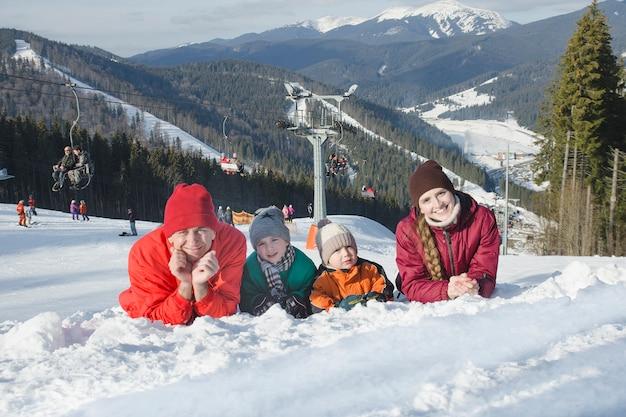 Padre, madre e due figli giacciono e sorridono sullo sfondo di una stazione sciistica Foto Premium