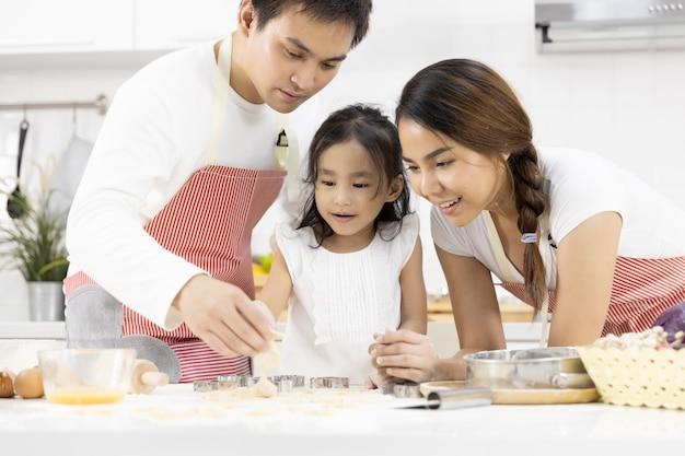 Padre, madre e figlia stanno preparando i biscotti in cucina Foto Premium