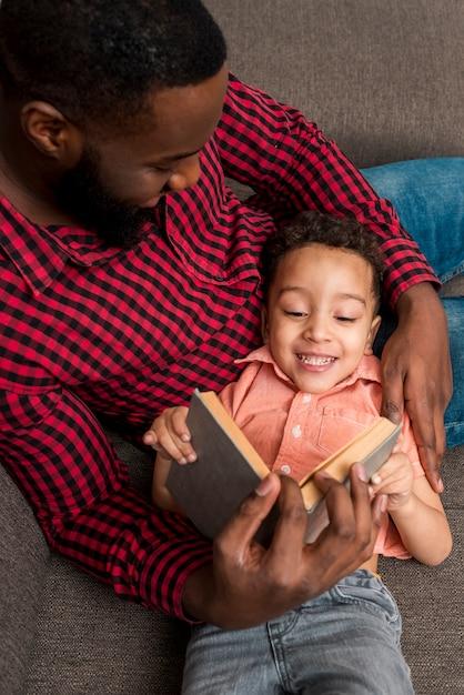 Padre nero e figlio carino leggendo il libro sul divano Foto Gratuite