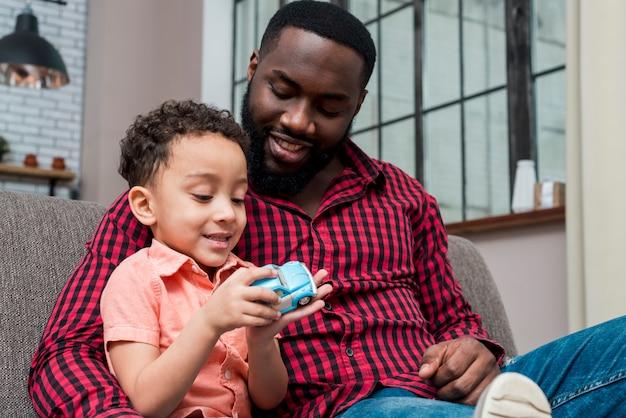 Padre nero e figlio che giocano con la macchinina blu Foto Gratuite